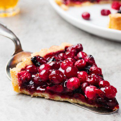 A piece of pie with jellied fresh cranberries.
